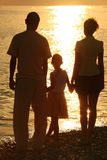 Silhuetas da família de encontro ao mar de lustro Foto de Stock Royalty Free