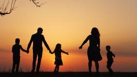 Silhuetas da família feliz que andam junto no prado durante o por do sol video estoque