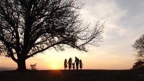 Silhuetas da família feliz que andam no prado perto de uma árvore grande durante o por do sol imagens de stock royalty free