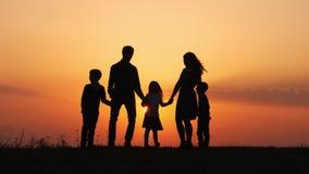 Silhuetas da família feliz que guardam as mãos no prado durante o por do sol vídeos de arquivo