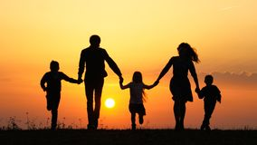 Silhuetas da família feliz que guardam as mãos no prado durante o por do sol fotografia de stock royalty free