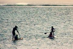 Silhuetas da fam?lia no por do sol no oceano Familysupping imagens de stock royalty free