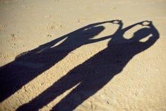 Silhuetas da fotografia dos pares ou dos dois amantes junto, sombra na terra, gesto da mulher um braço coração-dado forma, concei Imagem de Stock
