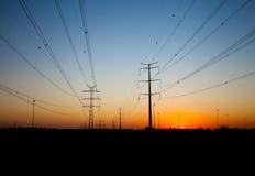 Silhuetas da linha de transmissão de energia polos no por do sol imagem de stock royalty free