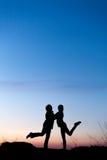 Silhuetas da mãe e da filha no por do sol bonito dusk foto de stock
