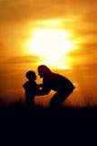 Silhuetas da mãe e do filho no por do sol Imagem de Stock