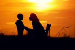 Silhuetas da mãe e do filho no sol de ajuste Fotos de Stock