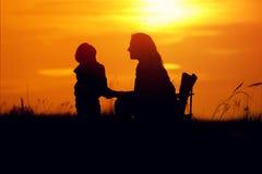 Silhuetas da mãe e do filho no sol de ajuste Imagem de Stock
