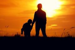 Silhuetas da mãe e do filho no sol de ajuste Foto de Stock Royalty Free