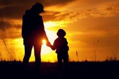 Silhuetas da mãe e do filho no sol de ajuste Fotografia de Stock