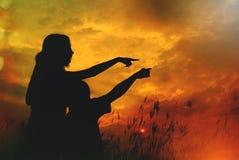 Silhuetas da mãe e do sol no por do sol Fotografia de Stock Royalty Free