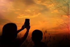 Silhuetas da mãe e do sol que tomam a imagem pelo telefone celular no por do sol Foto de Stock