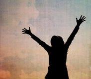 Silhuetas da mulher com mãos levantadas Foto de Stock