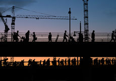 Silhuetas da ponte de cruzamento dos povos com fundo do céu do por do sol Imagens de Stock Royalty Free