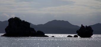Silhuetas da rocha no crepúsculo no mar Fotos de Stock