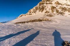 Silhuetas da sombra dos povos na neve Fotografia de Stock