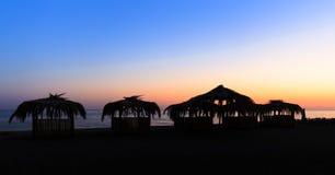 Silhuetas das choças com os telhados cobertos com as folhas de palmeira para o resto na praia no por do sol Imagem de Stock