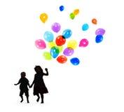 Silhuetas das crianças que jogam e que guardam balões Imagens de Stock