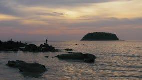Silhuetas das crianças que pescam em rochas em Tailândia - 4k grampo 1 video estoque
