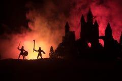 Silhuetas das figuras como os objetos separados, luta entre guerreiros no fundo nevoento tonificado escuro com o castelo gótico v imagens de stock royalty free