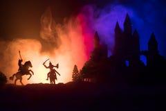 Silhuetas das figuras como os objetos separados, luta entre guerreiros no fundo nevoento tonificado escuro com o castelo gótico v imagens de stock