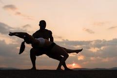 Silhuetas de dança ginástica misturada dos pares no por do sol Grace e beleza do corpo de ser humano Fotografia de Stock