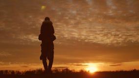 Silhuetas de dois caminhantes com trouxas que apreciam a opinião do por do sol da parte superior de uma montanha Apreciando a opi vídeos de arquivo