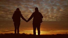 Silhuetas de dois caminhantes com trouxas que apreciam a opinião do por do sol da parte superior de uma montanha Apreciando a opi filme
