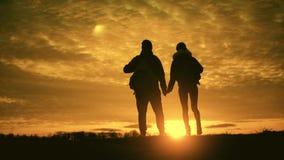 Silhuetas de dois caminhantes com trouxas que apreciam a opinião do por do sol da parte superior de uma montanha Apreciando a opi video estoque