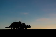 Silhuetas de dois dinossauros com fundo do por do sol Fotografia de Stock