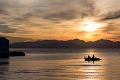 Silhuetas de dois homens no barco no nascer do sol em Corfu imagens de stock royalty free