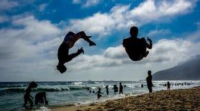Silhuetas de dois homens que executam saltos mortais na praia de Ipanema imagens de stock