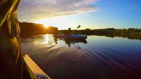 Silhuetas de dois homens que kayaking no por do sol, resto ativo, slowmo filme