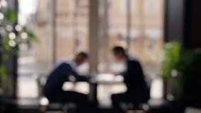 Silhuetas de dois homens que trabalham junto na tabela no escritório perto da janela vídeos de arquivo