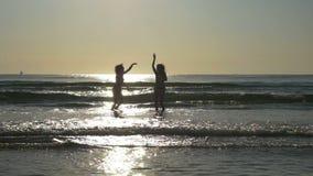 Silhuetas de duas amigas bonitas que têm o divertimento e que jogam no oceano no movimento lento filme