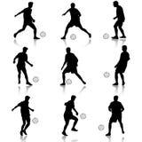 Silhuetas de jogadores de futebol com a bola Fotografia de Stock Royalty Free