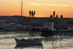 Silhuetas de jovens no molhe do mar Fotos de Stock