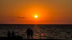 Silhuetas de jovens no por do sol e na parte dianteira de mar fotografia de stock