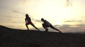 Silhuetas de pares da raça misturada de instrutores da aptidão que fazem os exercícios exteriores no fundo das montanhas rochosas vídeos de arquivo