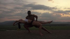 Silhuetas de pares musculares atléticos da raça misturada de ginastas que fazem exercícios ginásticos no por do sol no pico de mo vídeos de arquivo
