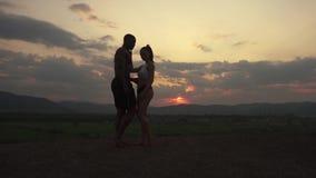 Silhuetas de pares musculares atléticos de instrutores da aptidão que dançam no por do sol no pico de montanha Nebuloso bonito filme