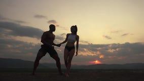 Silhuetas de pares musculares atléticos de instrutores da aptidão que fazem exercícios ginásticos no por do sol no pico de montan vídeos de arquivo