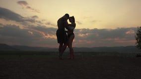 Silhuetas de pares musculares atléticos de instrutores da aptidão que levantam no por do sol no pico de montanha Nebuloso bonito video estoque