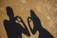 Silhuetas de recém-casados dos simbols do coração na praia Fotografia de Stock Royalty Free