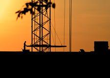 Silhuetas de um guindaste e de trabalhadores da construção em um fundo do por do sol imagem de stock