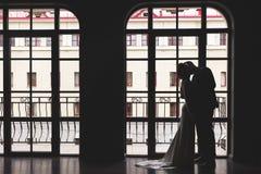 Silhuetas de um homem em um terno e de uma mulher em um vestido e com um ramalhete das flores que beija e que abraça-se próximo imagens de stock royalty free