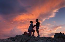 Silhuetas de um homem que faz a proposta de união a sua amiga Fotos de Stock