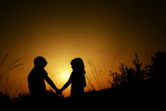 Silhuetas de um menino e de uma menina que guardam as mãos imagem de stock royalty free