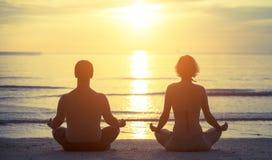 Silhuetas de um par novo que senta-se na posição de Lotus da ioga Fotografia de Stock Royalty Free