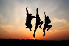 Silhuetas de um salto de três homens Imagem de Stock Royalty Free